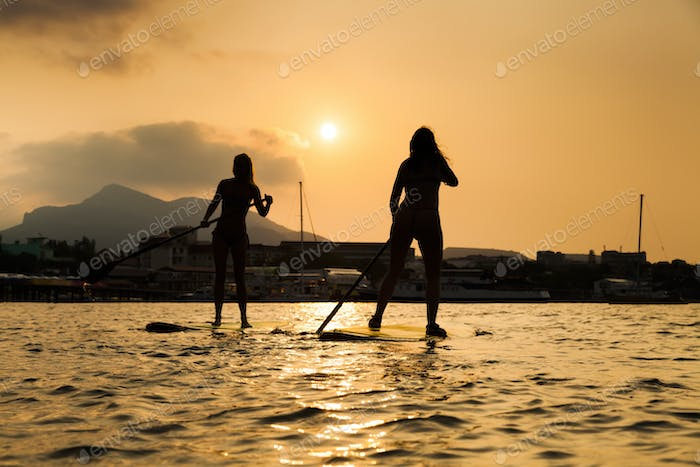 Silhouette of a beautiful woman on Stand Up Paddle Board. SUP