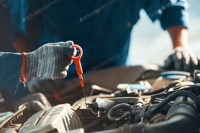 Mechanic checking motor oil level