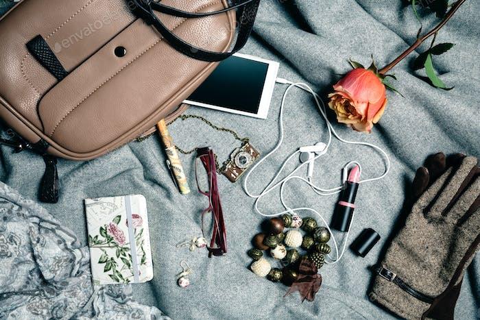 Feminine accessories from handbag over grey background