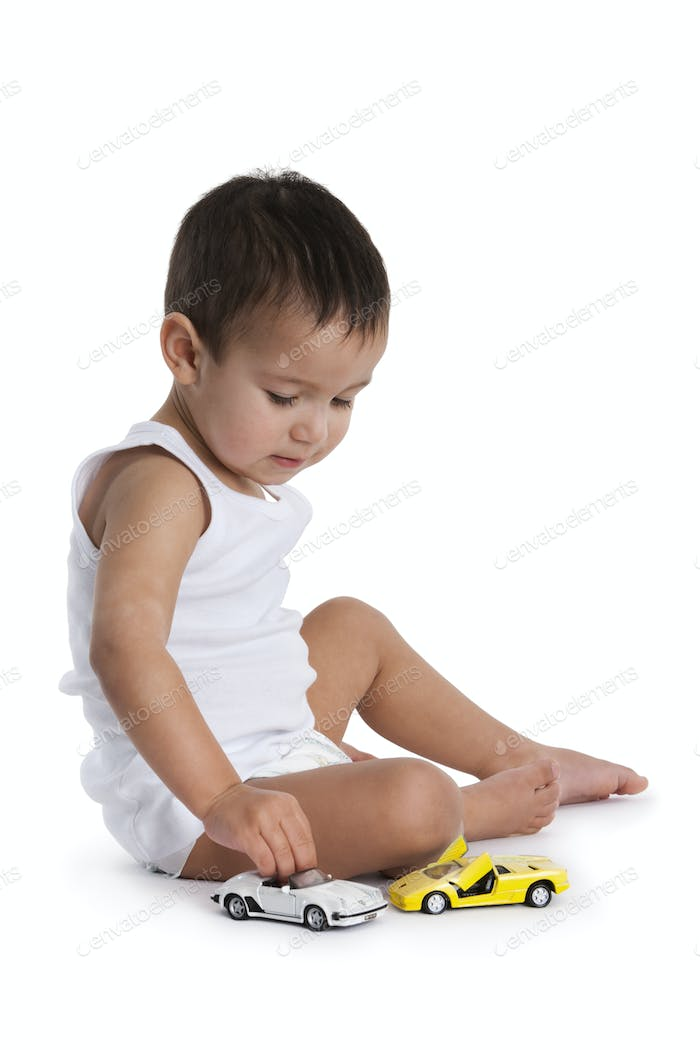 Toddler boy playing with toy cars on the floor