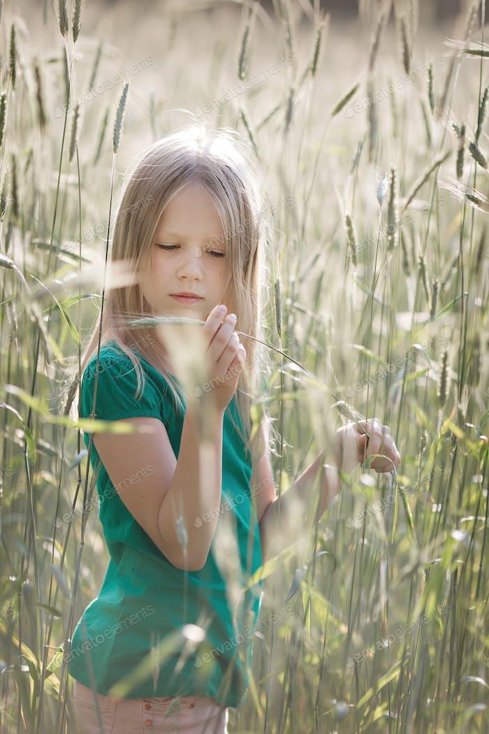 Girl on the field of ripe grain