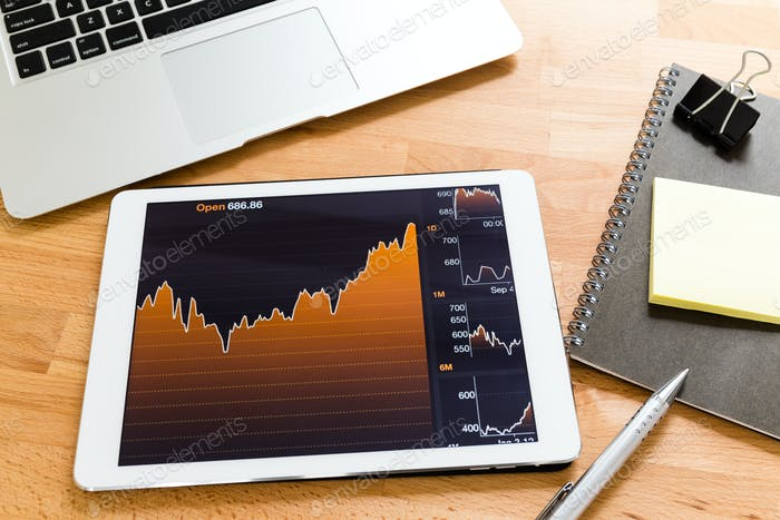 Tablet computer with financial chart on working desk