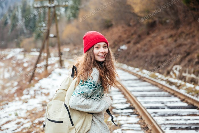 Smiling attractive young woman walking along railroad