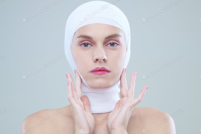 Woman touching face after surgery