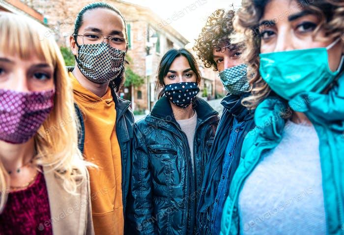 Comunidad de personas multirraciales cubiertas por mascarillas mirando a la cámara al aire libre