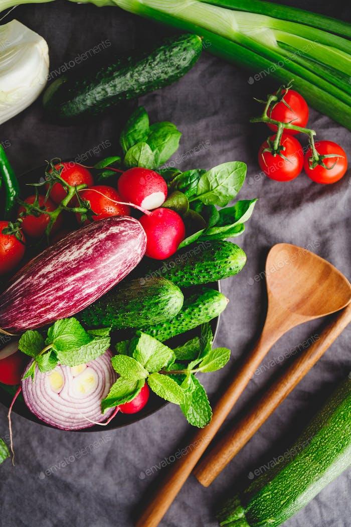 Verschiedene frisches buntes Gemüse in einem Teller auf einem Tisch mit hölzernen Küchenutensilien