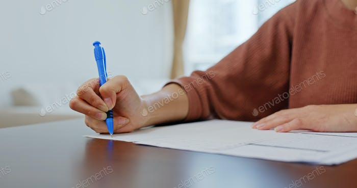 Woman write on paper, study at home