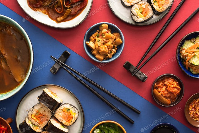 top view of chopsticks near ramen, kimbap and korean side dishes on blue and crimson