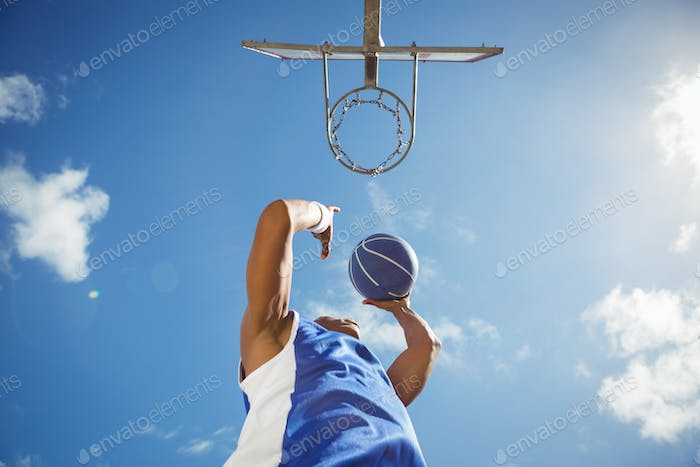Directly below shot of basketball player taking a shot
