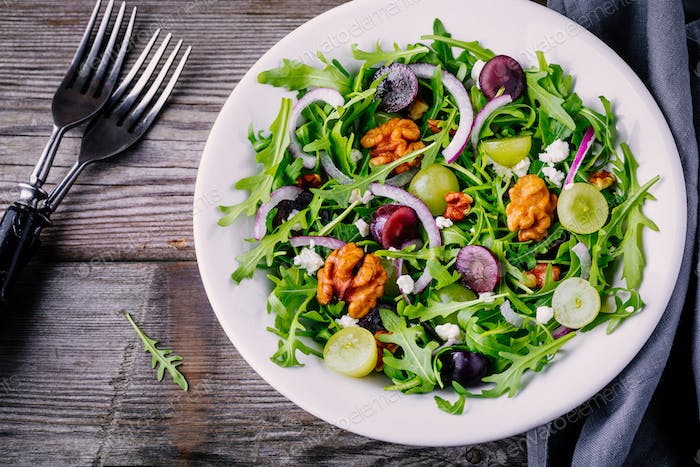 green salad bowl with arugula, walnuts, feta cheese, red onion and grapes