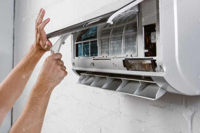cropped shot of repairman taking off filter from conditioner