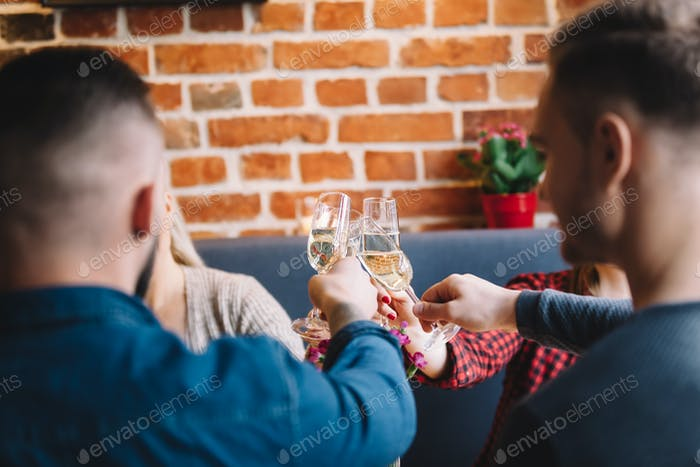 Four people raising glasses to toast.