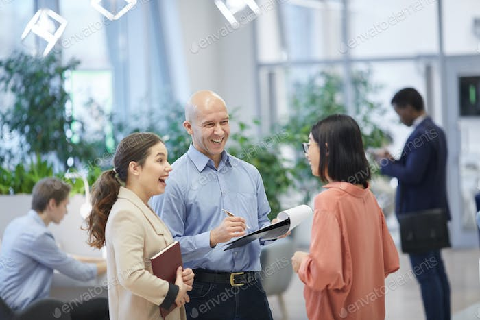 Smiling Manager Talking to Trainees in Office