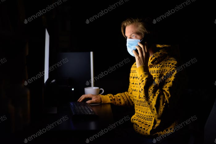 Young man with mask talking on the phone while working from home late at night in the dark