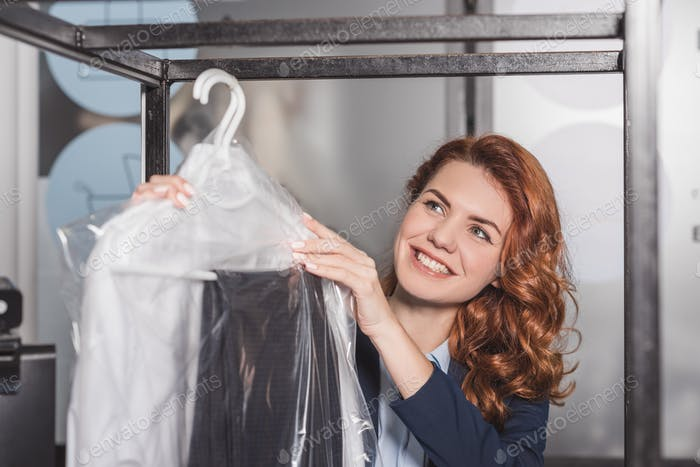 dry cleaning manageress hanging clothing in plastic bags