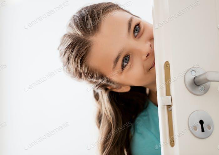 счастливая улыбающаяся красивая девушка за дверью дома