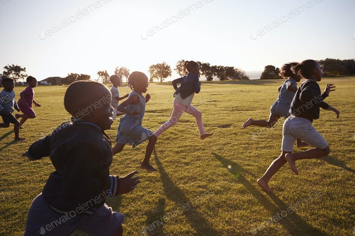 Elementary school boys and girls running in an open field