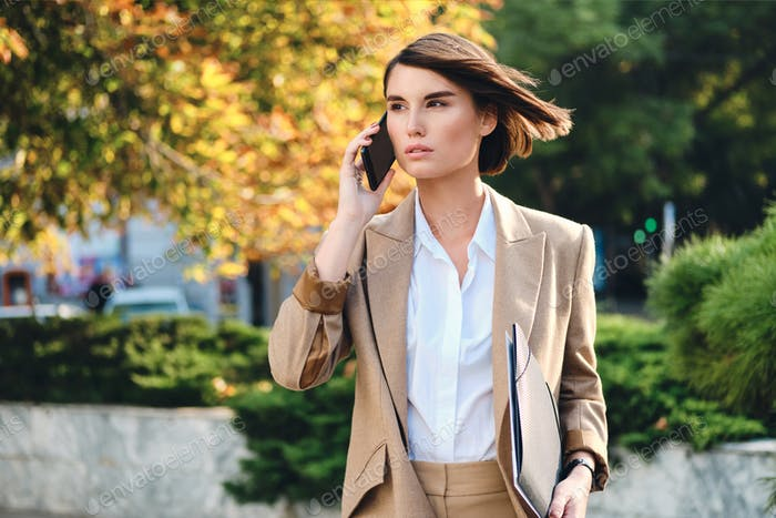 Young attractive stylish businesswoman talking on cellphone intently looking away on street