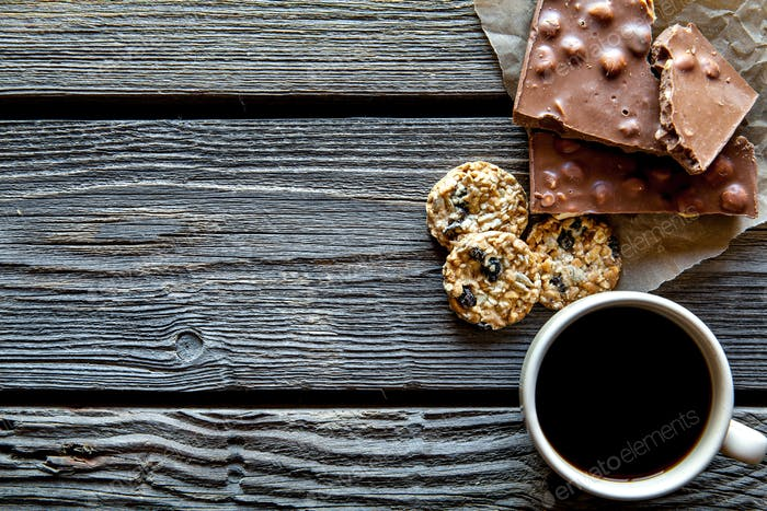 cup of coffee with a delicious chocolate and cookies on a wooden background