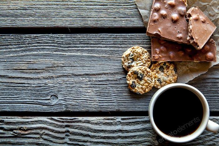 Tasse Kaffee mit einer köstlichen Schokolade und Kekse auf einem hölzernen Hintergrund