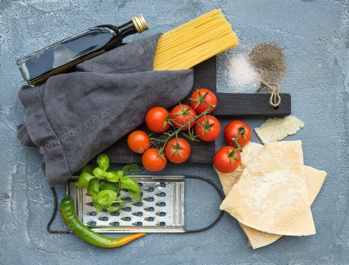 Ingredients for cooking pasta. Spaghetti, Parmesan cheese, cherry tomatoes, metal grater, olive oil