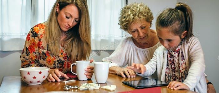 Drei weibliche Generationen nutzen Tablet und Smartphone
