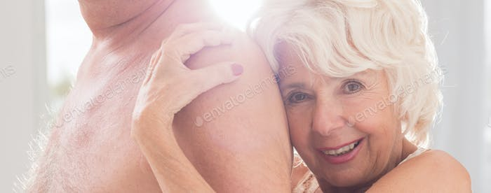 Senior woman hugging naked men's chest