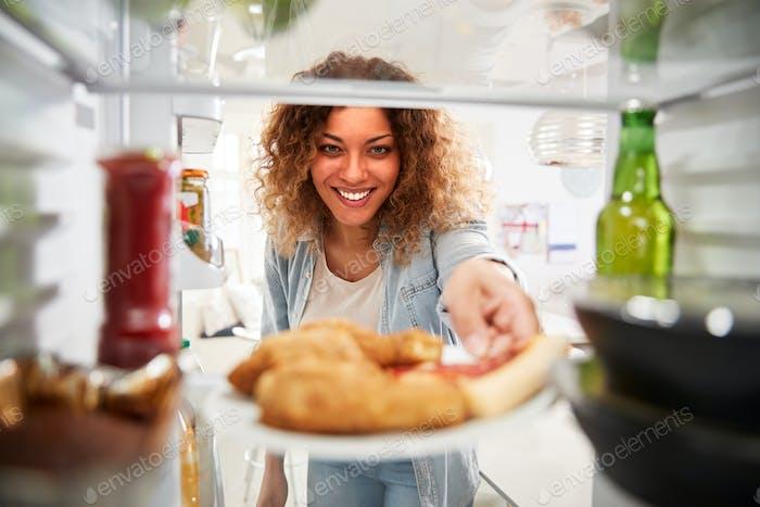 Blick aus dem Inneren des Kühlschranks gefüllt mit Essen zum Mitnehmen als Frau Tür öffnet