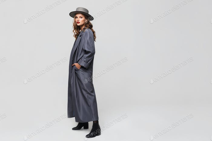 Young pretty woman in hat and cloak holding hands in pockets looking in camera over gray background