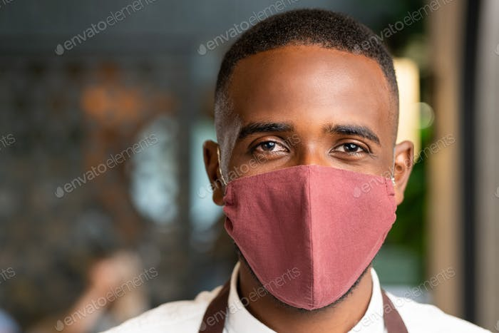 Head of young contemporary waiter of African ethnicity in protective mask