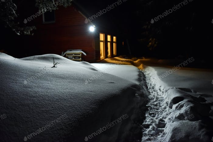 Winter night scene. Chimney light of a cottage illuminate the snow outside
