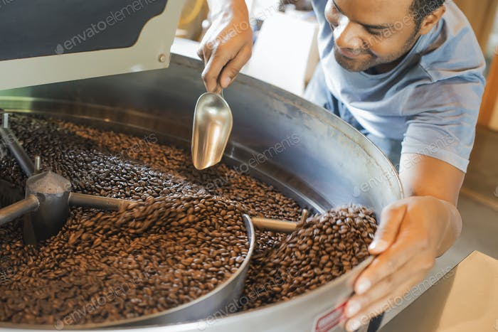 Maschinen an einer Kaffeebohne Verarbeitung Schuppen Rösten Kaffeebohnen wird von einem Mann überwacht.