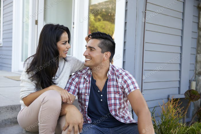 Affectionate Couple Sitting On Steps Outside Home