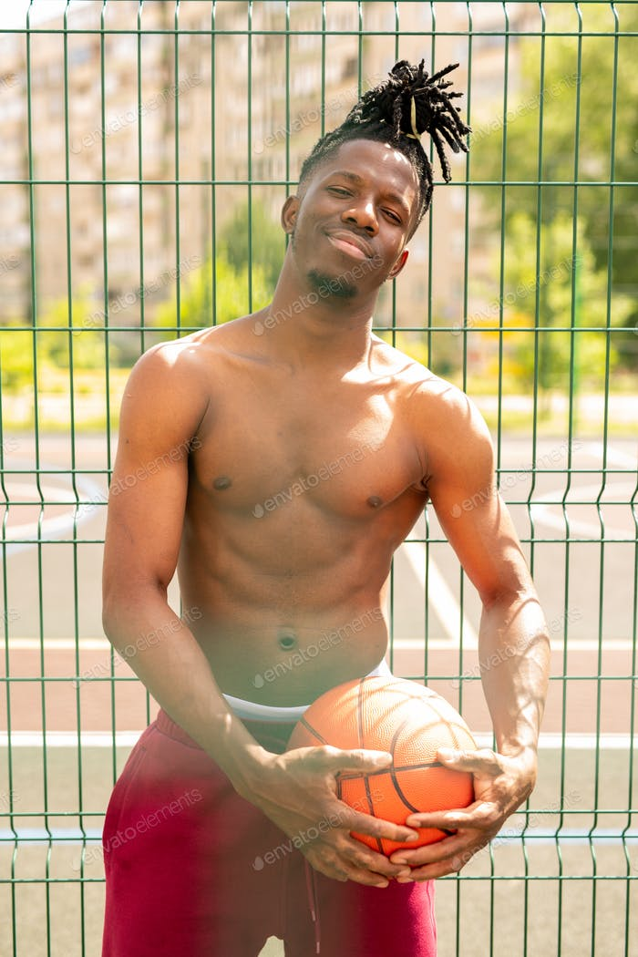 Happy young shirtless basketballer looking at you