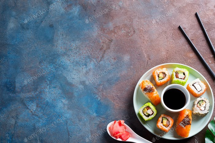 Various Fresh and delicious sushi set on ceramic plate with slate sticks, sauce on stone background