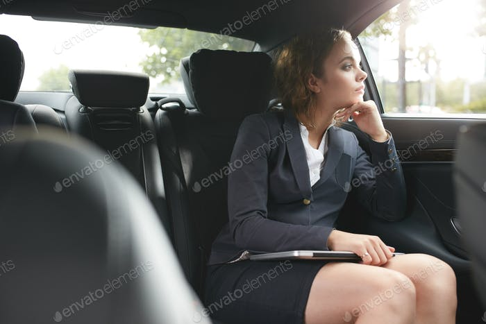Young businesswoman traveling to work in the luxury car