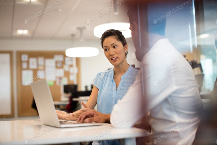 Businesswoman discussing with male colleague in office