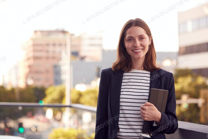 Portrait Of Businesswoman Holding Digital Tablet Outside Office Building With City Skyline