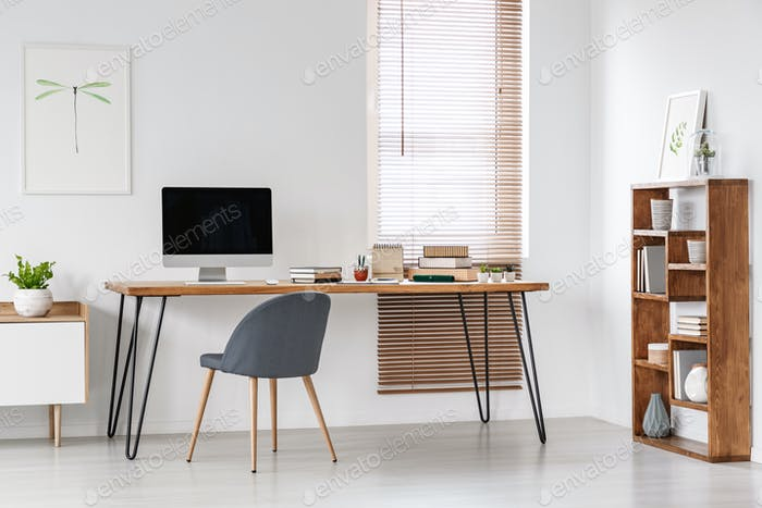 Grey chair at desk with computer monitor in minimal workspace in