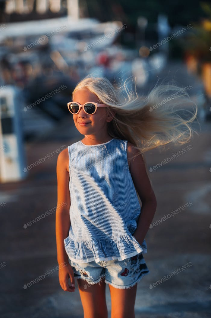 Portrait of a cute smiling ten-year-old girl with glasses.A girl in shorts and a blue t-shirt at