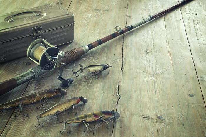 Antique Fishing Rod with Lures and Tackle Box on Wood Surface