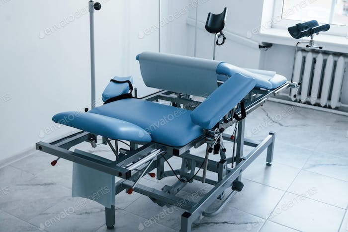 Blue colored obstetric bed indoors in the clinic cabinet at daytime