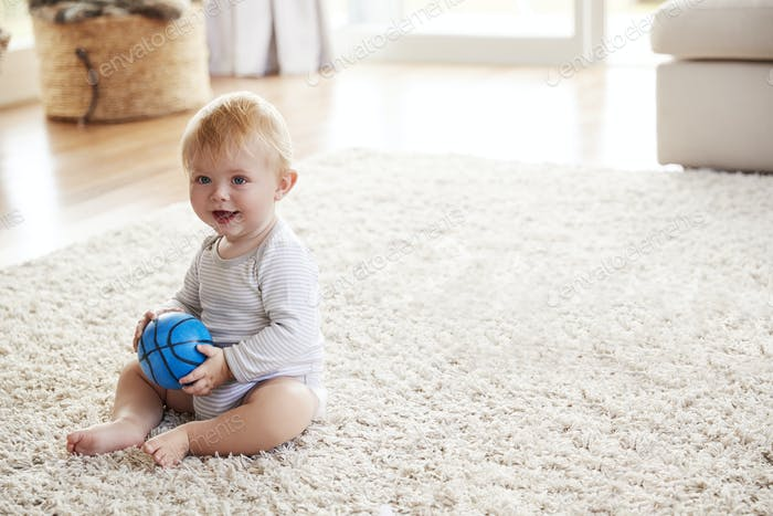 White toddler boy sitting on the floor in sitting room
