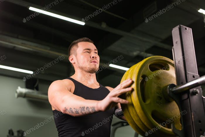 Young sportsman preparing his barbell by twisting power disk in.