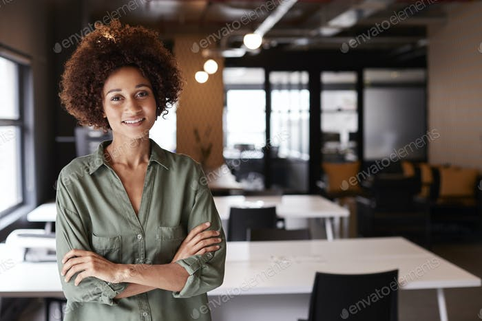 Millennial black female creative standing in an open plan office with arms crossed smiling to camera
