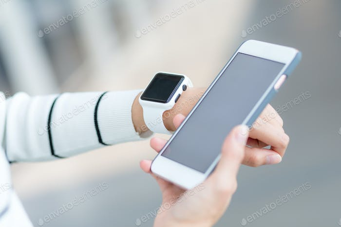 Woman wearing smartwatch and connecting to cellphone