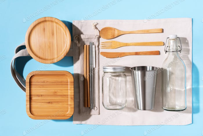 Cotton bags, glass jar, bottle, metal cup, straws for drinking, bamboo cutlery and boxes on blue