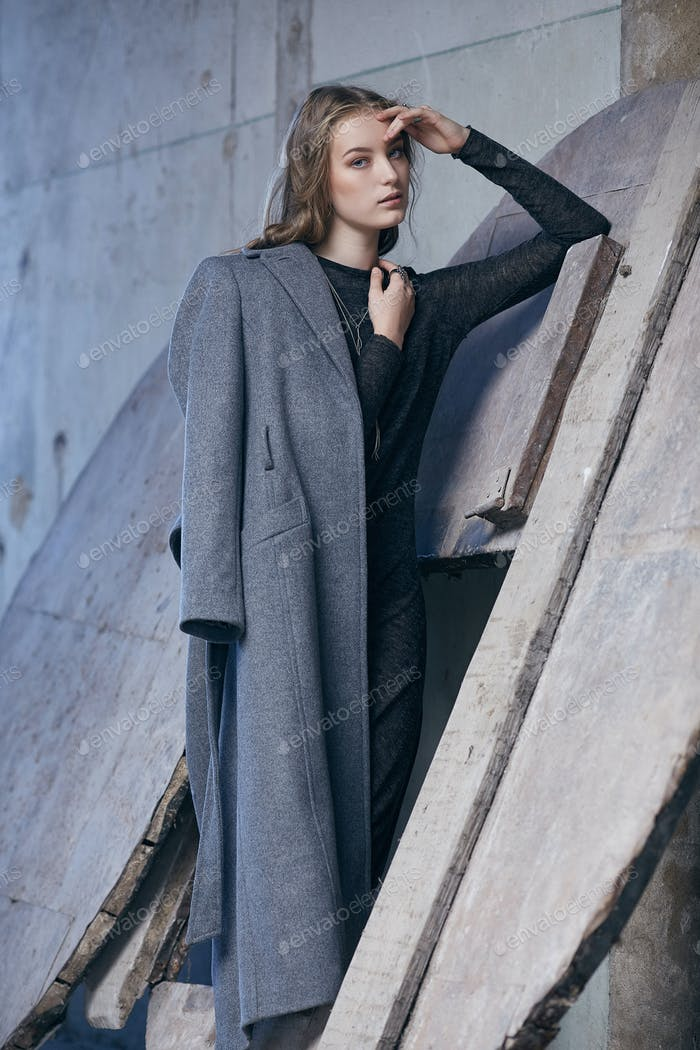 A  lady in a long grey jacket.
