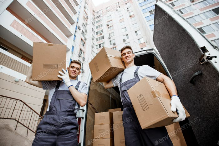 Two young handsome smiling workers wearing uniforms are standing in front of the van full of boxes