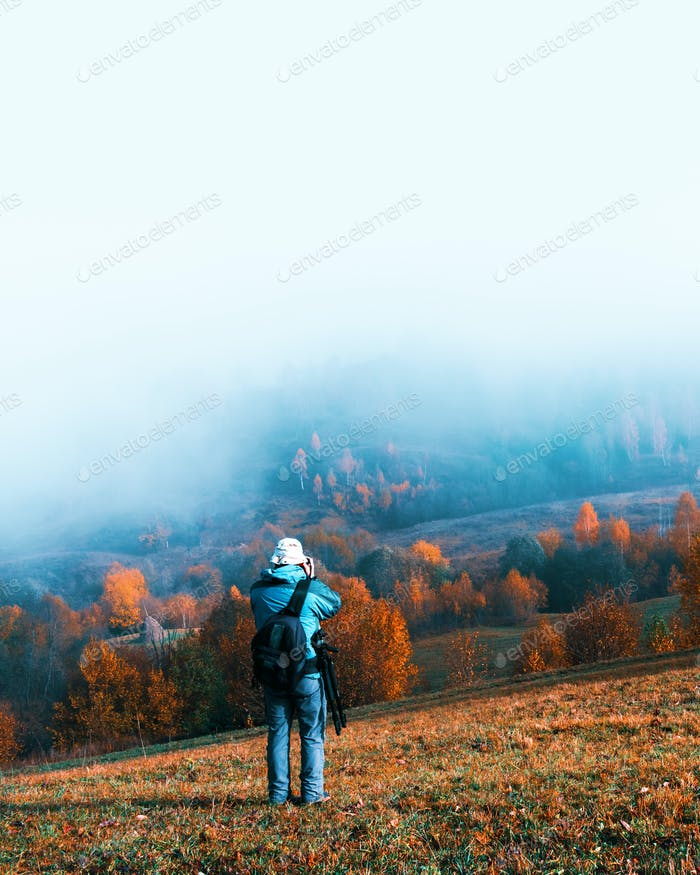 Photographer taking photo of autumn landscape